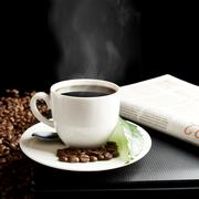 Cup of black coffee with mist with laptop,newspaper, green coffee leaf, coffe - stock photo