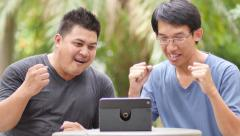 Asian men watching a game on tablet Stock Footage