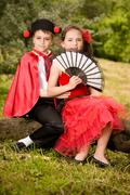 Portrait of a very young couple in spanish style garment having fun in a meadow. - stock photo