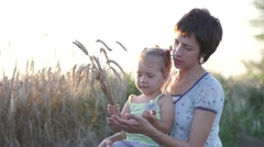 Mum with a small daughter and a bunch of ripe wheat ears at sunset Stock Footage