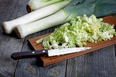 sliced cabbage and shallots on a rustic table - stock photo