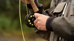 Man Reeling in a Fish from a River Stock Footage