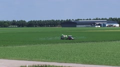 Tractor spraying field in flat polder landscape, North East Polder Stock Footage