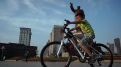 Boy riding a bike past statue of Mao zedong Stock Footage