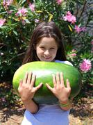 smiling little girl with an enormous WATERMELON - stock photo