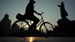 Man riding a bicycle past statue of Mao zedong Stock Footage
