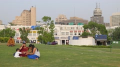 Woman and child sitting in park at Connaught Place,New Delhi,India Stock Footage