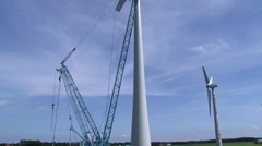 Tilt up old and new wind turbine at construction site Stock Footage