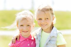 happy little girls hugging outdoors at summer - stock photo