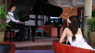 Stock Video Footage of Bride looking at groom who is playing the piano