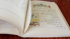 Thumbing through a book in arabic - stock footage