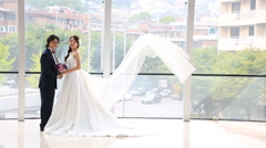 Bride and groom standing in front of window against bright background Stock Footage