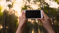 Woman taking a picture of the sunset in the bamboo forest Stock Footage