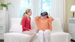 Young attractive woman shows her elderly mother how to use head-mounted display. Stock Footage
