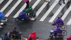 People wearing colorful rain coat, riding bikes on zebra crossing in raining day Stock Footage
