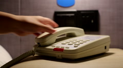 Hand picking up telephone and pressing the dialing keys Stock Footage