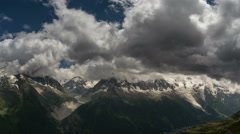 Aguilles du Chamonix above village and valley dark clouds time lapse 4k Stock Footage