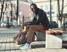 Fashion elegant young african man wearing a sunglasses and black leather jack - stock photo