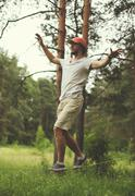 Sport, leisure, recreation and healthy lifestyle concept - man slacklining wa Stock Photos