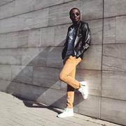 Street fashion, stylish young african man wearing a sunglasses and black leat - stock photo