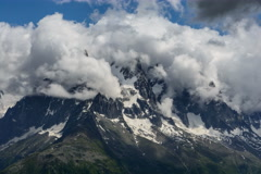 Stock Video Footage of Aiguille des Grands Charmoz Chamonix being covered in churning clouds time lapse