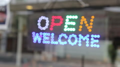 'Open Welcome' led flash light sign on a storefront window Stock Footage