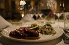 Food and drink, fancy dining room, plate with red meat, rice and veggies. Stock Photos