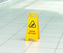 Yellow sign that alerts for wet floor Stock Photos