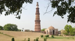 View on tower of victory at Qutb Minar through trees,New Delhi,India Stock Footage