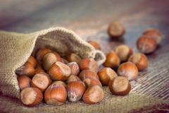 A bag of hazelnuts on wooden table - stock photo