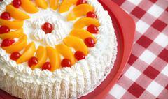 Homemade cream cake with peaches and cherries - stock photo
