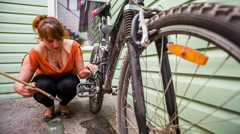 Young Girl Cleaning Her Bicycle With Brush And Liquid Stock Footage