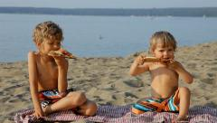 Little boys eating pizza on the beach Stock Footage