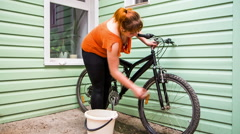Young Girl Washing The Bicycle Wheels Stock Footage