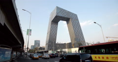 video of the iconic Beijing CCTV headquarters and busy freeway Stock Footage