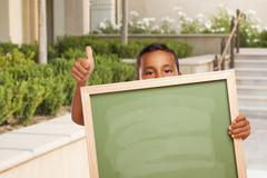 Boy with Thumbs Up Holding Blank Chalk Board on Campus Stock Photos