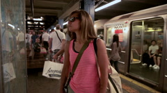 pretty tourist in pink tank top and shoulder strap bag looking at subway map NYC - stock footage