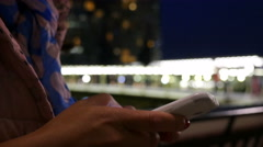 Woman using smart phone at night in Canary Wharf, London, hands only - stock footage