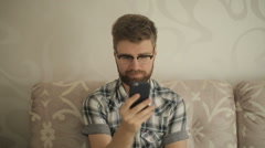Bearded man in glasses uses a smartphone at home Stock Footage