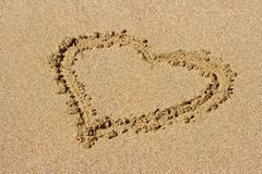 Heart drawn on beach sand - stock photo
