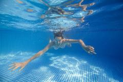 Underwater woman in swimming pool Stock Photos