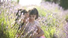Mother and child communicate each other in lavender field at sunset Stock Footage