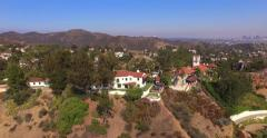 Camera flying up over Hollywood Hills capture aerial view Los Angeles cityscape Stock Footage