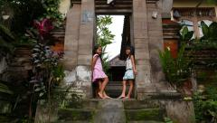 Balinese children standing smiling at stone gate, tilt camera Stock Footage
