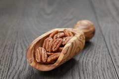 dried pecan nuts in olive scoop on wood table - stock photo