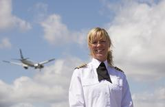 Portrait of a pilot with a passenger jet in the sky Stock Photos