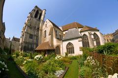 Garden with a medieval church Stock Photos