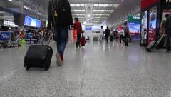 Passengers pulling luggage walking in railway station Stock Footage
