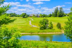 Golf place with pond and custom built luxury big house on background - stock photo