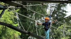A boy walks through a suspension bridge, he wears an arnes and a helmet. Stock Footage